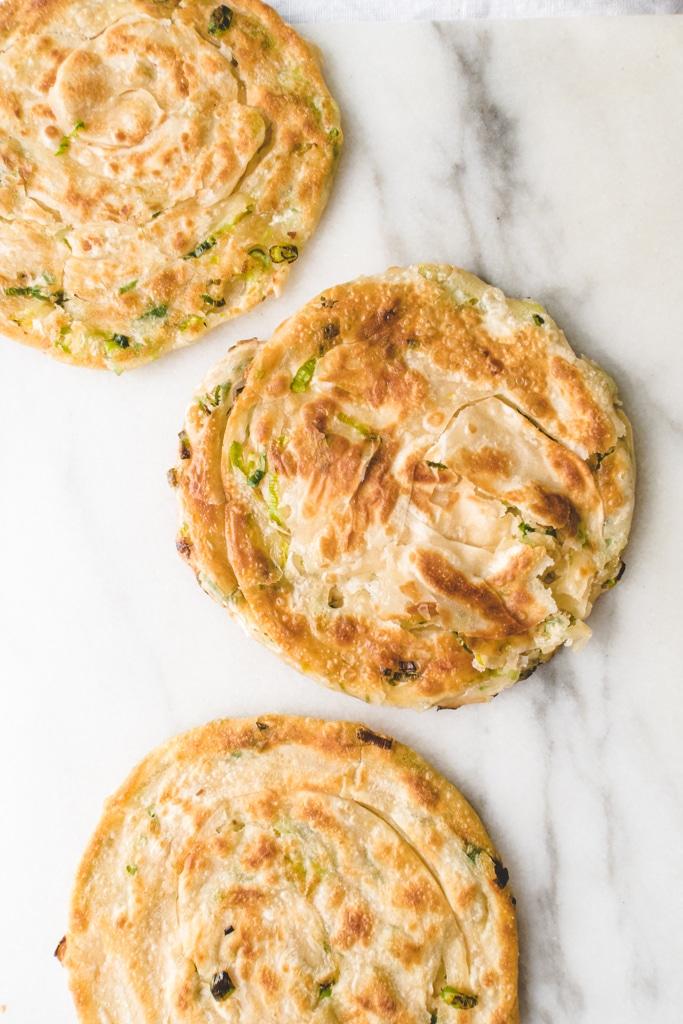 three crispy and flaky scallion pancakes.