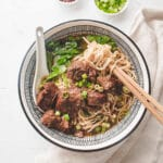 Taiwanese beef noodle in a bowl with spoon and chopsticks.