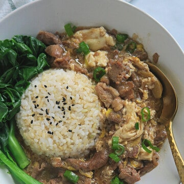 beef and egg stew rice bowl with leafy greens.