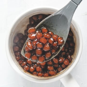 brown sugar boba pearl in a sauce pan with grey spatula.