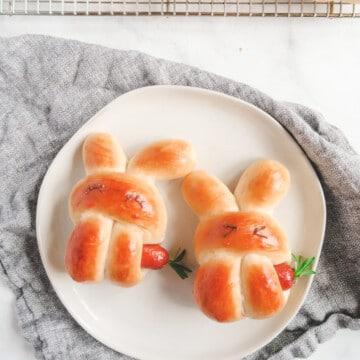 two bunny sausage buns on a plate.