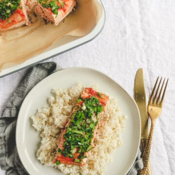 mayo ketchup baked salmon with fresh herbs on top serve over rice in a white plate with fork and knife on the side.