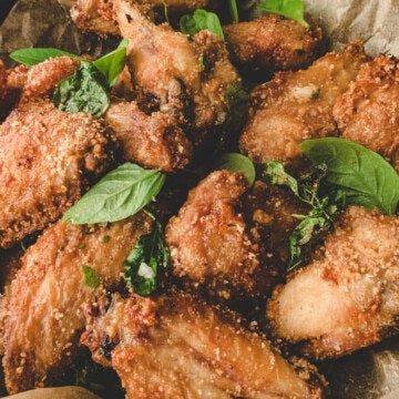 air fry chicken wings and basil on parchment paper in a black skillet.