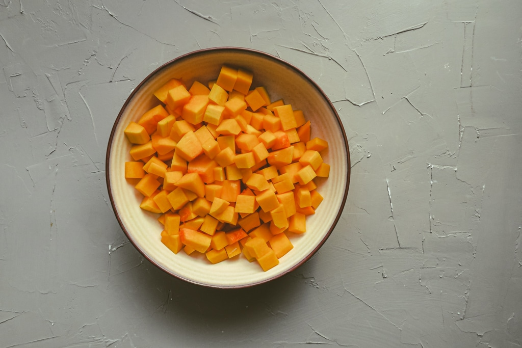 bowl of cubed butternut squash against a gray background.