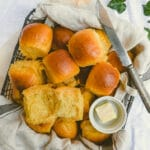 yellow bread rolls, butter and butter knife in a black basket lined with dish towel.