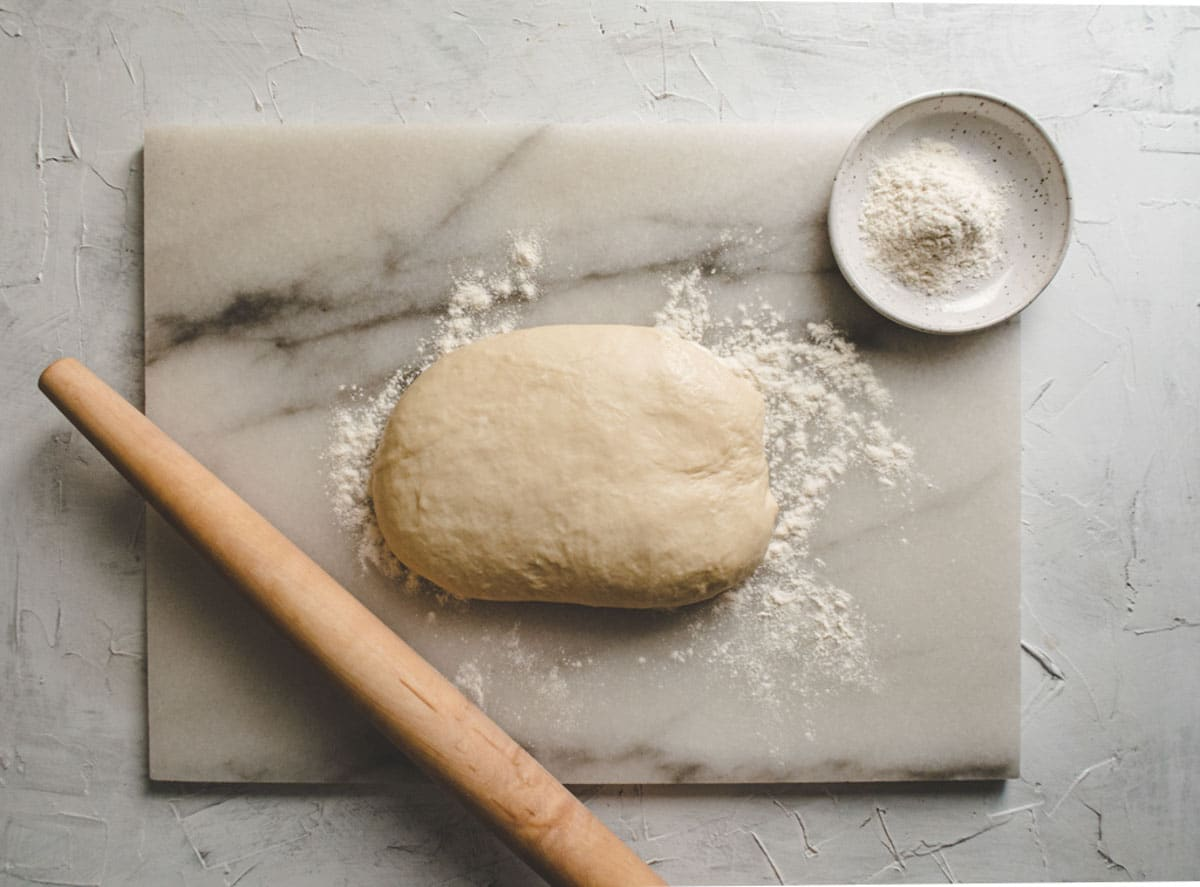 shaobing dough on a marble board with flour and rolling pin.