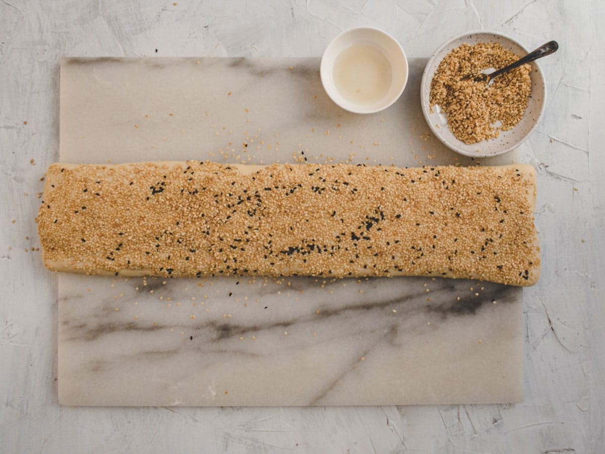 folded shaobing dough with black and white sesame seeds on top on a marble board
