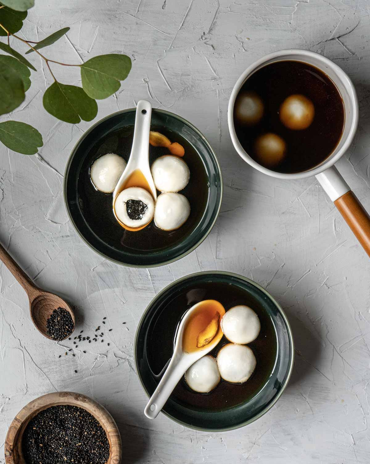 Two bowls and one sauce pan with tang yuan in it and a bowl of black sesame seeds on the side.