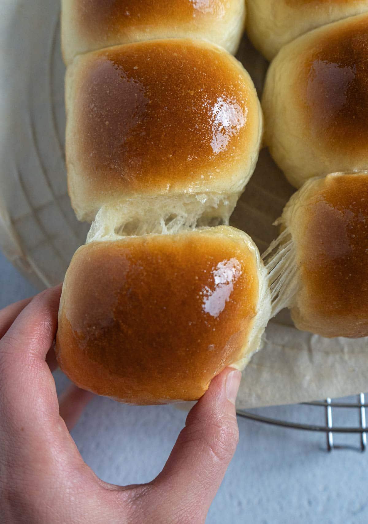 hand pulling a milk bun.