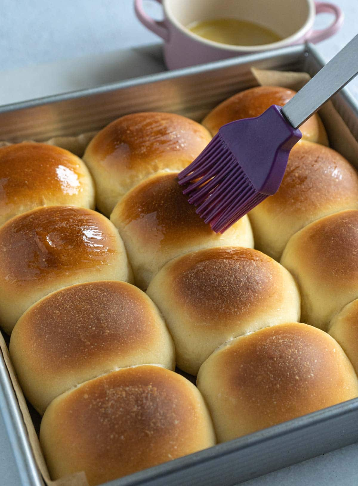 Brushing butter on the surface of milk buns.