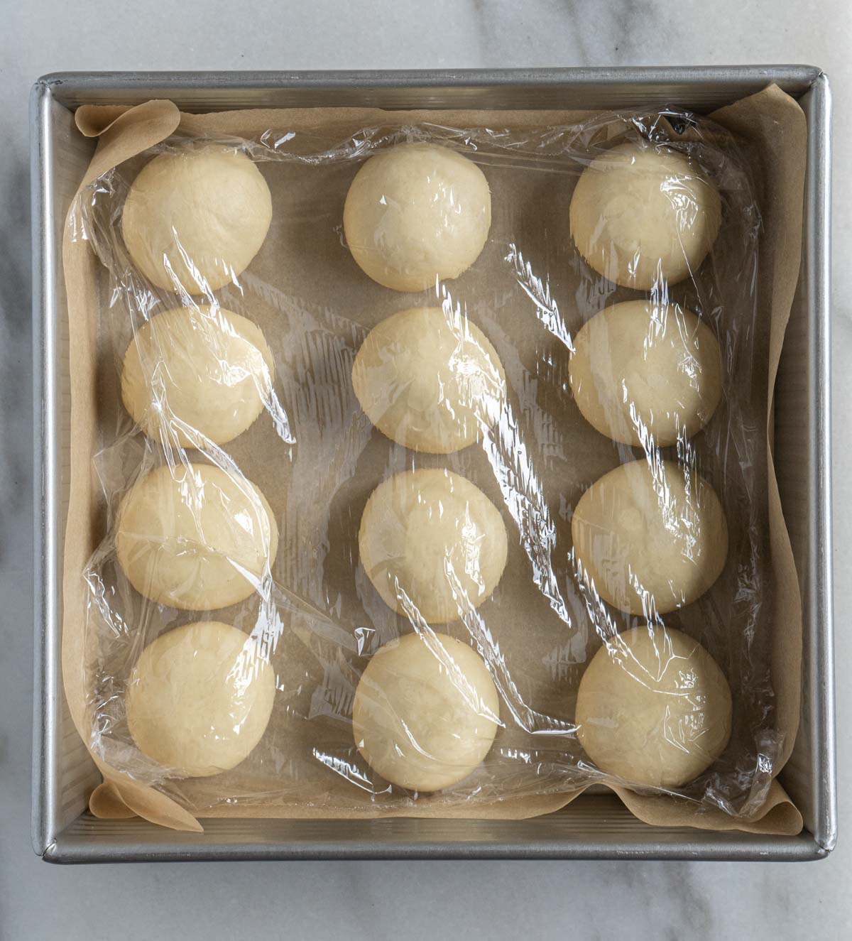 milk bun dough covered with plastic wrap before second proof.