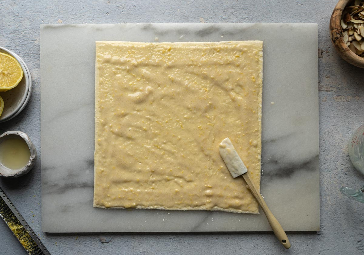 Spraying egg white/sugar mix on the puff pastry sheet with a small spatula.