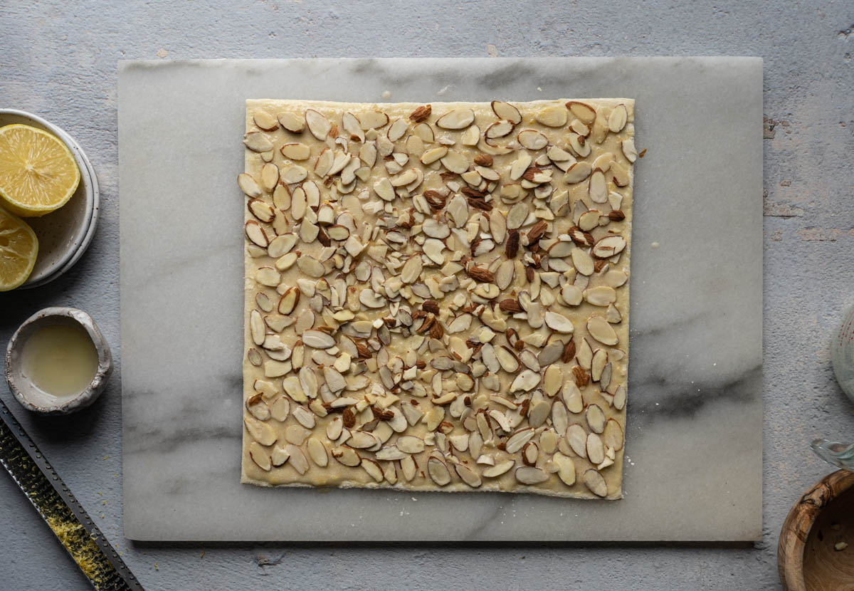 Top the puff pastry sheet with almond slices.