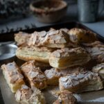 almond puff pastry cookies in a baking tray with a wood bowl. plant and a grey cup.