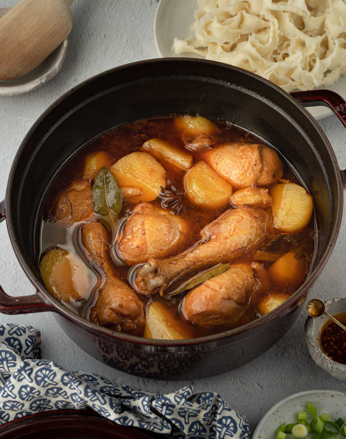 A pot of Chinese chicken stew with potatoes with a plate of cooked noodles on the side.