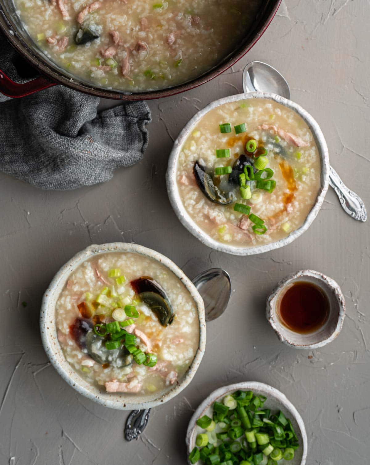 a pot and two bowls of century egg congee, a small bowl of sesame oil, and a plate of chopped scallion.