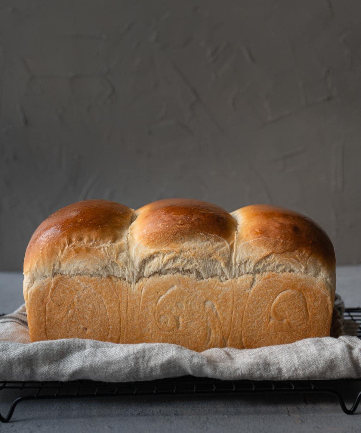 Milk bread loaf on a cooling rack.